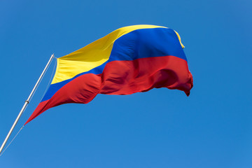 colombian flag being move by the wind over sky and clouds on a sunny day.