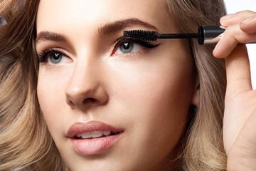 woman doing her makeup eyelashes black mascara