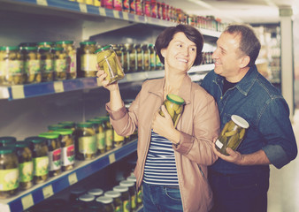 Portrait of an elderly couple selecting a pickles at the grocery