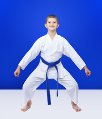 Athlete with a blue belt is in the rack karate