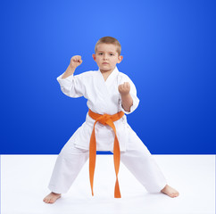 Boy in karategi worth in rack karate