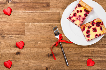 Raspberry cake on white plate and red hearts on wooden background. Valentines Day background