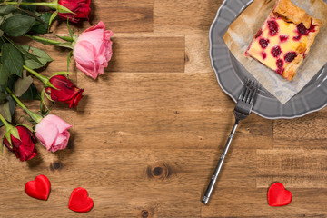Raspberry cake on grey plate, roses and red hearts on wooden background. Valentines Day background