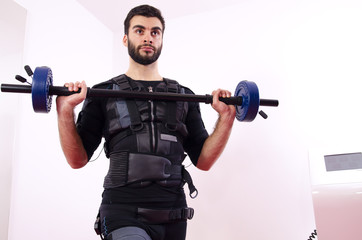 Closeup of muscular man lifting weights, chest exercise on EMS machine