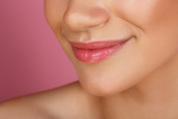 Beautiful smile with whitening teeth. Dental photo. Macro closeup of perfect female mouth, lipscare. Perfect pink lip makeup. Perfect clean skin, light fresh lip make-up. Pink background