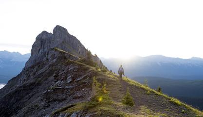 Male hiker walks along ridge of mountain during sunrise