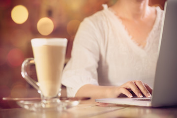 Modern woman working online in vintage coffee shop..Start new day  with a cup of coffee and laptop computer,bokeh background,selective focused