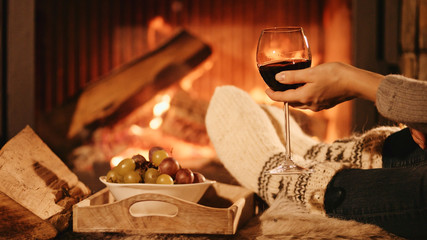 Woman by the fireplace. Woman in woollen socks taking a glass of