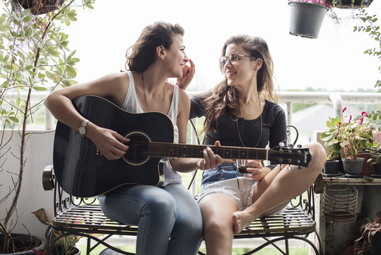 Young couple playing guitar outdoors