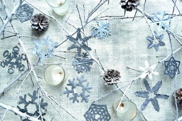 Silver snow flakes paper cut out with candle light.frame