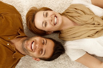 Happy couple lying on carpet side by side