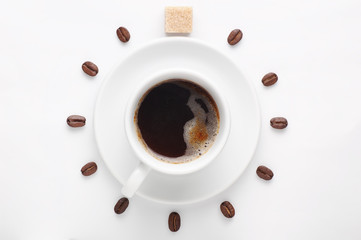 Coffee cup and coffee beans with cane sugar cube against white background forming clock dial viewed from top