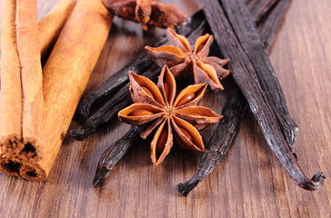 Closeup of star anise, fragrant vanilla and cinnamon on wooden surface plank