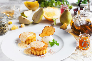 Plate with sweet cupcakes and ice-cream ball on table. Served dessert of muffins with cream topping and pear slice on white dish. Restaurant menu, confectionery, pastry concept