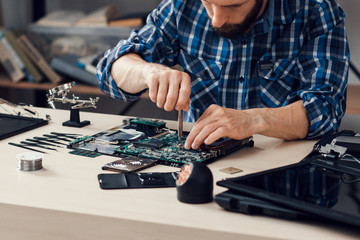 Laptop disassembling with screwdriver at repair shop. Engineer fixing broken computer motherboard. Electronic renovation, technology development concept