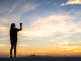 Girl photographer with camera at sunset
