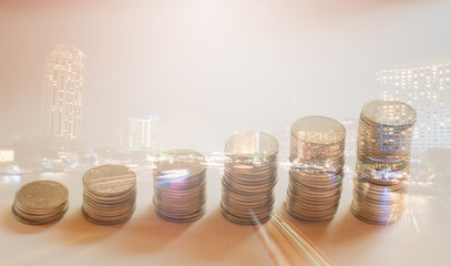 Double exposure rows of coins with city view, finance and banking concept
