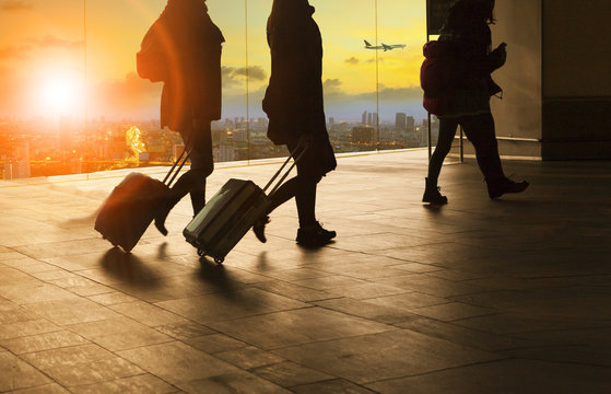 people and traveling luggage walking in airport terminal buildin