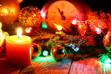 New Year`s card with Christmas tree fir branches, midnight clock, burning candle, golden balls, garland lights on vertical old wooden desk table background.