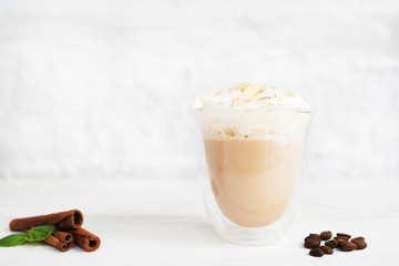 Glass of latte with cinnamon sticks and coffee beans. Cup of creamy cappuccino on white background, free space for text or advertisement