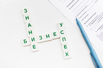 Russian scrabble words on business concept with pen and contract paper. Featured words are: Knowledge, Business, Success. Isolated with free space