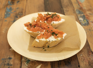 Salmon and cream cheese sandwiches on a wooden table