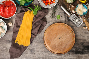 Blank round old kitchen board with ingredients for cooking pasta