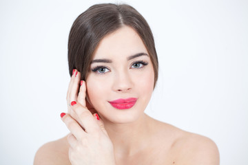 Beautiful Young Woman with Fresh Clean Skin touch own face. Red lips, red lipstick. Cosmetology, beauty and spa.