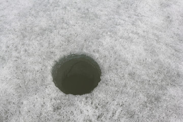 Hole for subglacial fishing on a river surface
