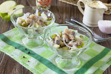Festive salad with pickled herring, vegetables and apple. Appeti