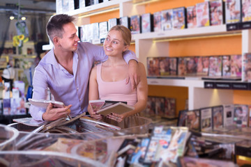 Happy  family couple selecting erotic video and smiling