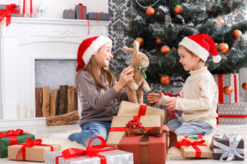 Happy children in santa hats unwrapping christmas presents