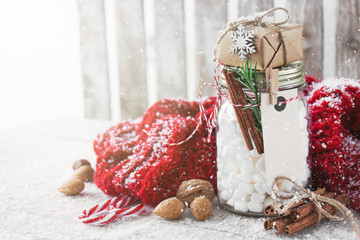 Jar with marshmallow and small gift with christmas decorations,