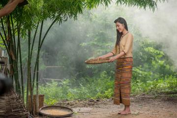 Beautiful Thai Asian women winnow rice separate between rice