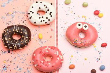 Funny glazed donuts on pink background