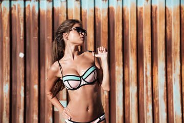 Woman in swimwear and sunglasses standing over rusty metal background