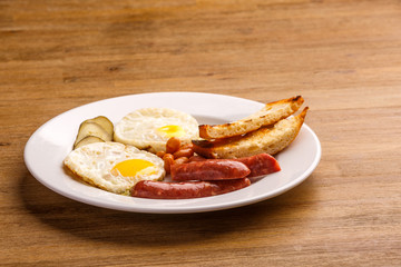 Fried eggs with bacon sausages and greens