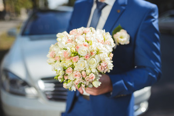 Groom with Flowers at Car