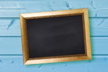 Chalkboard in vintage frame on blue wooden wall background