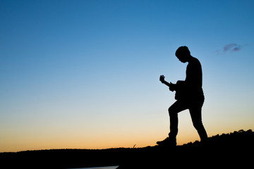 silhouette of musician with guitar at sunset field, music concept
