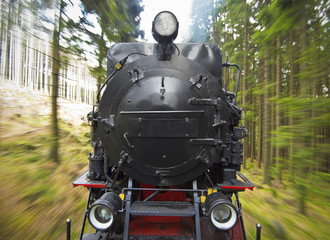 front view of a historic German black steam powered railway train in motion blur, National Park Harz, Germany