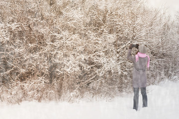 Woman photographs the winter forest