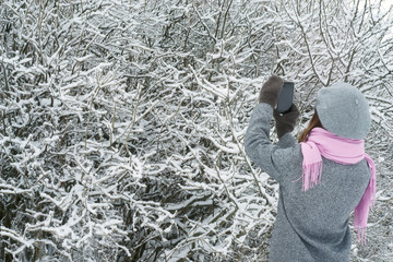 Woman takes photos of the snow-covered trees