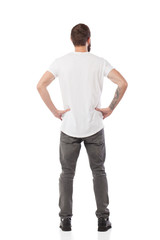Back pose, full length shot of a young man looks ahead isolated