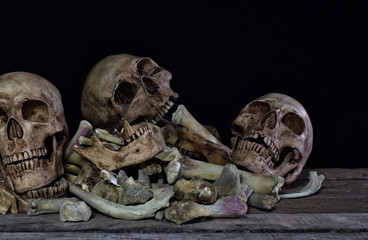 Three skull and pile of bone on old wooden plate