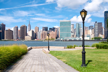 The midtown Manhattan skyline on a summer day seen from a beautiful park in Queens