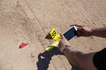 forensic hand use mobile phone take picture of evidence with evidence marker