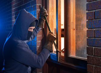 Burglar Using Crowbar To Break Into a House at night with room left and right for type - fototapety na wymiar