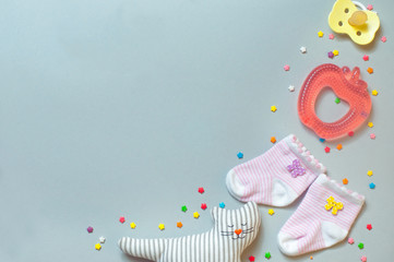 Socks, soother, teether and sleeping cat toy over grey backgroun