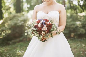 Bride holding a wedding bouquet on a sunny wedding day